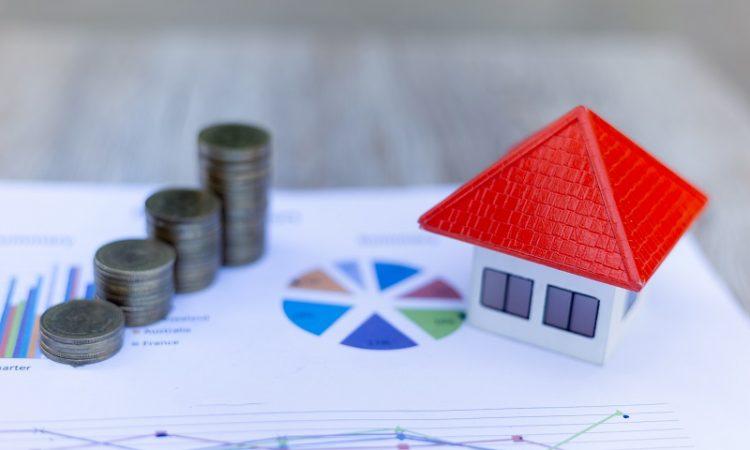 kartka z wykresami, na której stoją stosy monet i model domu